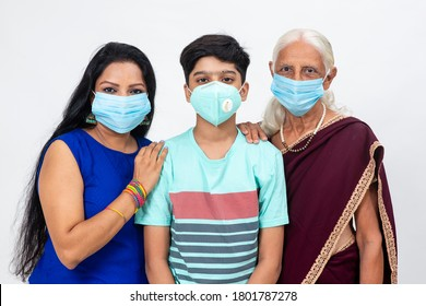 Indian grandmother, daughter and son wearing Covid-19 protection mask. Happy Indian family standing and looking into the camera