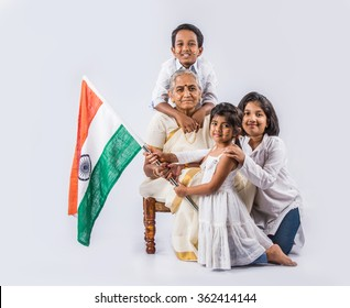 indian Grandmother and kids celebrating republican day or Independence day with faces painted with tricolour while holding national flag, isolated over white background