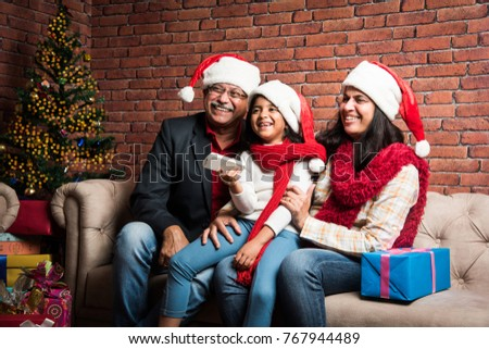 indian grandparents and grand daughter celebrating christmas while watching television and clicking selfie