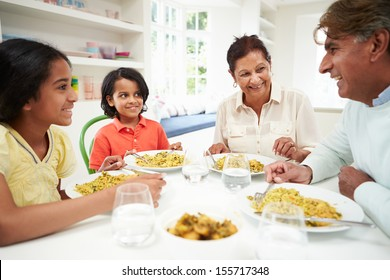 Indian Grandparents And Grandchildren Eating Meal At Home