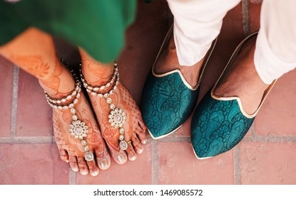 Indian Groom and bride showing foot Khussa shoes and jewelry