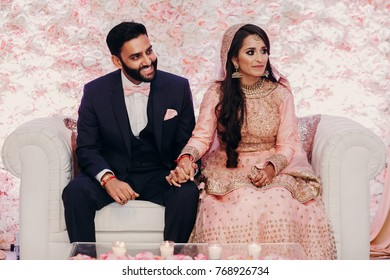Indian groom in classy western suit and bride in pink Hindu dress sit on white couch