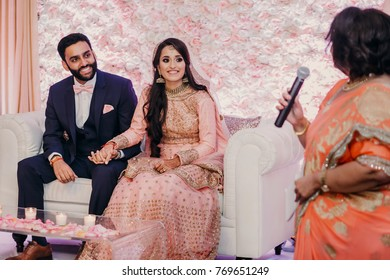 a83cbcd6d4 Indian groom in classy western suit and bride in pink Hindu dress sit on  white couch