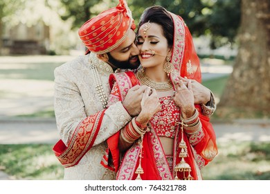 Indian groom dressed in white Sherwani and red hat with stunning bride in red lehenga stand and hold each other tender while they hug