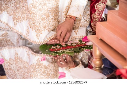 Indian groom helps the bride in touching the seven betel nuts with her right toe