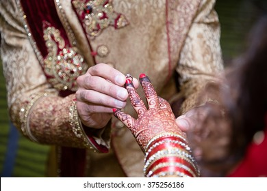 Indian groom putting ring on indian bride