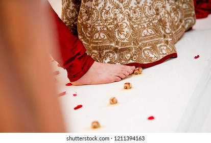 Indian groom touches with toe seven nuts or betel