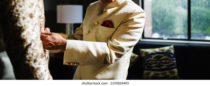 Indian groom's father assisting with the sherwani prior to the ceremony
