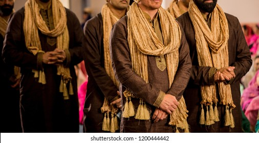 Indian groomsmen at wedding ceremony wearing brown Shalwar Kameez and Golden Dupatta. Karachi, Pakistan - October 11, 2018.