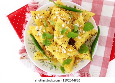 Indian gujarati Traditional Street Food Khaman Dhokla snack made from chick pea flour and rava Served With sev and Chilli