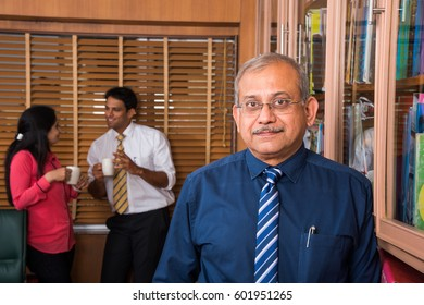 indian handsome senior businessman standing with arms in pocket while 2 young business people having coffee and discussing in the background