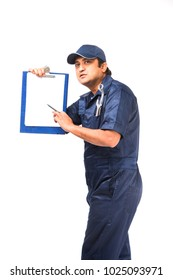 Indian happy auto mechanic in blue suit and cap holding spanner tool with laptop or check list or writing pad or using smartphone