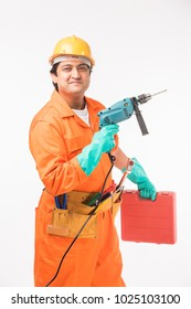 Indian happy electrician or worker or handyman in orange uniform with yellow hard hat and tools belt, standing isolated over white background