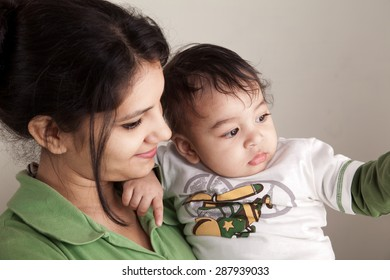 Indian happy mother and baby boy looking at others over gray background