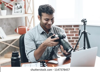 Indian Happy Young Man Photographer Work from Home Using Technology Editing Photo with Laptop. Creative Male Hipster in Casual Wear Focusing on Freelance Work. Business People Concept.