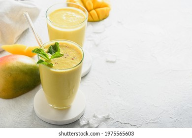 Indian healthy ayurvedic mango lassi on gray background with copy space. Close up. Freshness mango lassi made of yogurt, water, spices, fruits and ice.