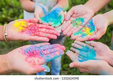 Indian holidays, fun and Holi festival concept - Female palms covered in different colors