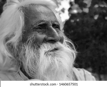 Indian holy old man on a roadside with white beard in black and white in Mcleodganj,Himachal Pradesh ,India on 7th sep 2014