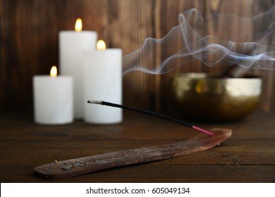 Indian incense stick with smoke on wooden background closeup