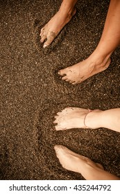 An Indian and Italian traveller rest their feet in the dark coloured sands of Nosara, Costa Rica after a long day of surfing.