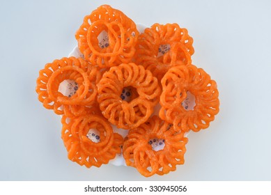 Indian jalebis arranged in flower shape in white plate on white background, top view. favorite pastry item in Kerala, India. Dewali sweet, fried crispy dessert. yellow, brown, orange jalebis .