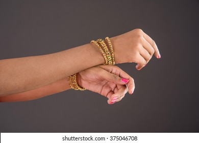 Indian Jewellery - Closeup of girl wearing traditional designer gold bangles/bracelets and showing graceful dance poses of hand over dark background, selective focus