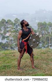 Indian Kalaripayattu warrior with shield poses for a photo during Kalaripayattu marital art demonstration in Kerala, South India