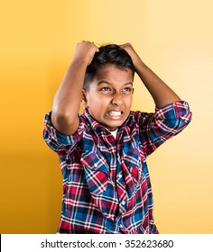 indian kid and headache or cephalalgia, standing isolated over yellow background