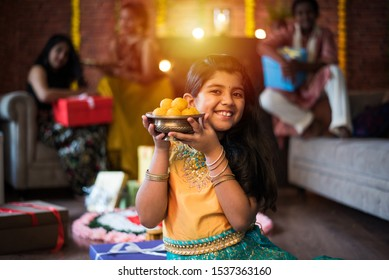 Indian Kids celebrating Diwali / Deepawali, Bhai Dooj or Rakhi / Raksha Bandhan with flower rangoli, gifts, diya