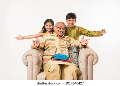 Indian kids with grandfather sitting on a sofa while wearing traditional cloths on some festival day sharing gifts and sweets