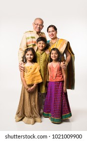 Indian kids with grandparents in traditional cloths, standing isolated over white background