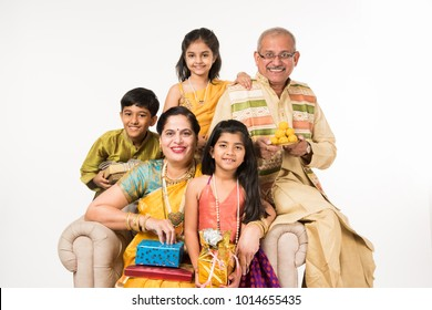 Indian kids with grandparents in traditional wear holding gifts, sweets and puja or pooja thali or taking selfie, isolated over white background