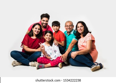 Indian Kids with parents / grandparents, sitting isolated over white background, studio shot
