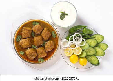 INDIAN KOFTA CURRY with salad and yogurt, Meatballs in glass bowl. horizontal top view on white background.