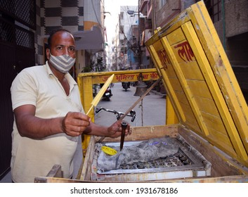 Indian Kulfi vendor wearing protective mask giving Kulfi to a customer. Kulfi is a frozen dairy dessert originating in the Indian subcontinent  Delhi - India 8th March 2021