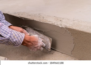 Indian labour levelling plastered side wall of a floor using flat trowel and cement manually, Stock image.