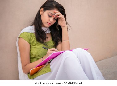 Indian late teen girl student sitting near wall and doing study. She is reading and writing on book in outdoor at day time. She is wearing traditional dress