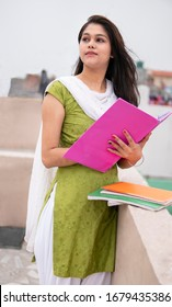 Indian late teen girl student standing on rooftop and doing study. She is looking and thinking while reading on book in outdoor at day time. She is wearing traditional dress