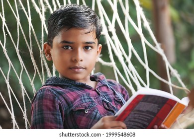 Indian little boy reading book lying on the hammock outdoors