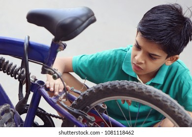 Indian Little Boy repairing cycle