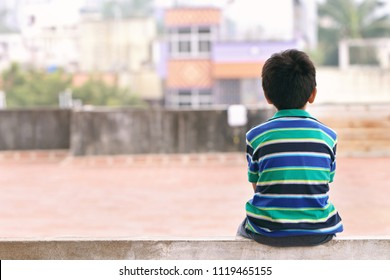 Indian Little Boy Sitting on The Wall