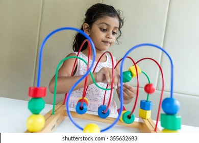 Indian little girl play with the wried loop of wooden bead