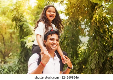 Indian little girl sitting on her fathers shoulders