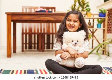 Indian little girl sitting with teddy bear and smiling