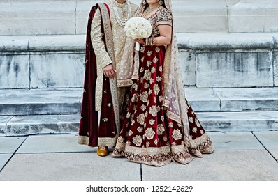 Indian lovebirds showing wedding dress and bride holding bouquets
