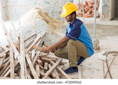 indian male contractor on site using hammer