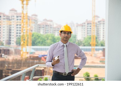 indian male engineer inspecting site with construction background