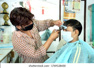 An Indian male hair dresser cutting hair in his beauty saloon with proper safety measures for Covid-19.Cutting hair of a man in mask. Hair care during Covid-19.Beauty saloon opens after lock down.