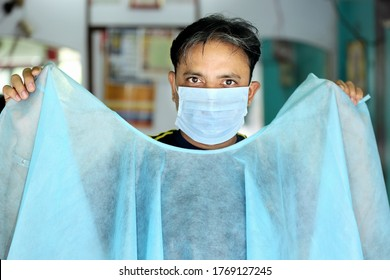 An Indian male hair dresser in mask showing disposable apron for hair and beauty care with proper safety measures for Covid-19. Safety measures in salons. Beauty saloon opens after lock down.