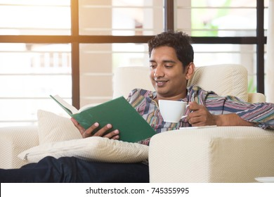 indian male having coffe and reading on a sofa